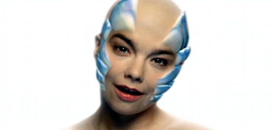 Björk: Hunter, Still aus dem Videoclip: Die Sängerin Björk steht mit Glatze vor weißem Hintergrund und hat stahlblaue Animationen am Kopf. (© 1997 björk overseas ltd/one little indian records ltd)